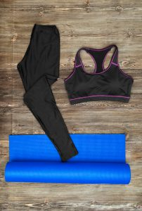 Woman's yoga outfit on wooden background